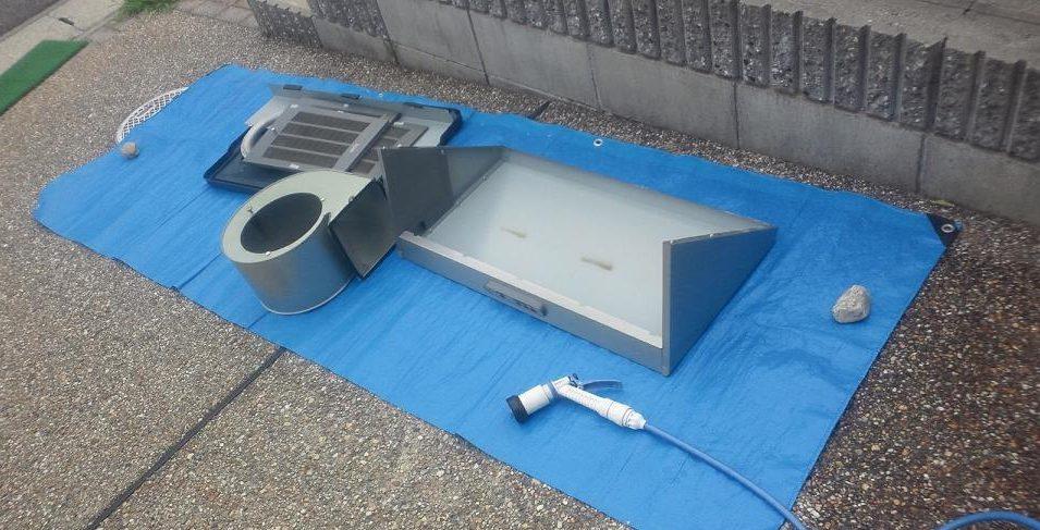 外で洗っている換気扇の部品