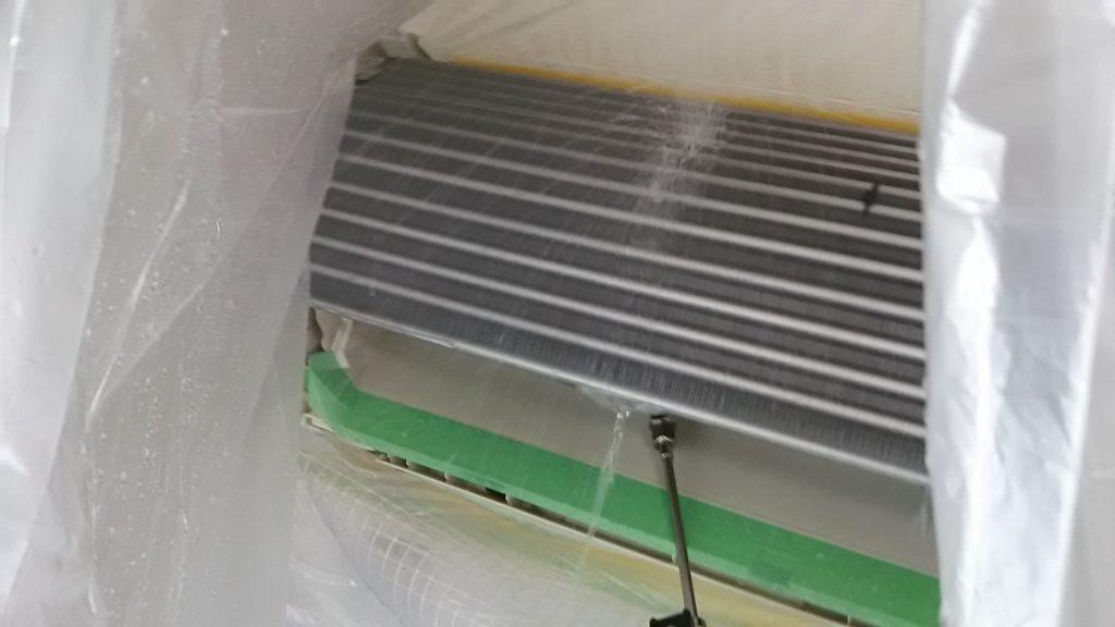 エアコン内部から外に向かって高圧洗浄中