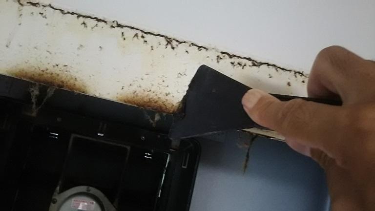 ヘラでレンジフードの油汚れを落とす